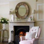 Round mirror with heavy-weight metal installed over white marble fireplace mantel a white washed round wood side table with white decorative vase an armchair in pink a pair of smaller table lamps