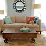 Rustic-Coffee-Table-London-with-wheels-on-the-flower-pattern-of-the-carpet-and-sofa-with-colorful-pillows-and-rounded-mirror-on-the-soft-blue-wall-between-two-table-lamps