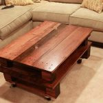 Rustic-Coffee-Table-with-wheels-in-fron-of-beige-sofas-and-on-beige-carpet-and-orange-pillows