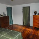 Simple Bedroom With Grey Bed And Two Dark Door Curtains Two Wooden Cabinets With Drawers