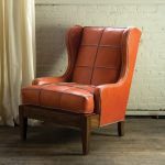 Simple but elegant orange leather reading chair design with wooden base and legs