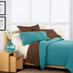 Simple modern unfinished wooden bed frame with low headboard teal and brown bedding with pillows an unfinished wood bedside table combination with beautiful blue glass vase and plants