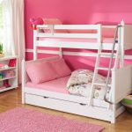 Simple white bunk design for twin little girls an open shelves for organizing shoes and some decorative items a rattan basket a pink bedroom rug