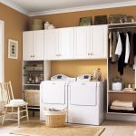 Simple white wall cabinets with under shelves and single shelf on right side two units of machine for washing and drying clothes a wooden chair a rattan basket
