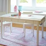 Simple wood craft desk for kids with drawers a pair of white painted wood chairs for kids an area rug with sea cucumber motifs