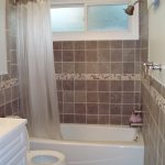 Small Bathroom Interior With Wall Mount Shower Faucet And White Tub Toilet Cabinet
