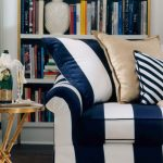 Striped White And Black Couch With Piilows And Bookcase