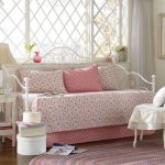 Sweet Pink Bedding For White Coated Iron Daybed In Classic Style Three Decorative Pillows Round Light Pink Area Rug White Wood Side Table With Table Lamp