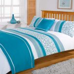 Teal and white bedding with pillows wooden bed frame with wooden headboard white wool rug for bedroom