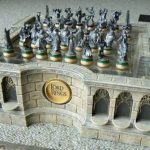 The Lord Of The Ring Chess Set With Castle Like Chessboard And Detailed Characters For The Pieces Near Black Box On The Grey Carpet