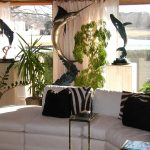 Tropical Theme Inside Living Room With White Coach And Black Striped Pillows