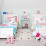 Two sets of single bed with higher headboard for little twin girls a light blue console table as bedside table a large bedroom rug with colorful stars pattern two pink storage boxes