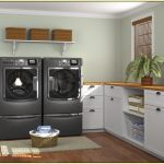Under cabinet units with shelves in the center and wooden countertop two big laundry machines a rattan storage basket white mat for laundry room