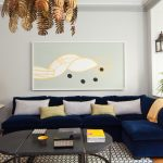 Velvet sectional in blue navy color option  some accent pillows in various colors an area rug with modern pattern a grey coffee table hexagonal side table for displaying yellow cap table lamp