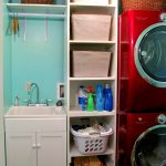 Vertical rack idea with boxes and plastic baskets as storage units a single under cabinet with sink and faucet a rod over the sink a washing machine unit a dryer machine unit in red two rattan boxes