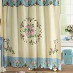 Victorian-Blue-Shower-Curtain-with-Pink-Rose-Design-and-blue-towels-on-the-white-bathtub-and-flowers-in-white-vase-also-white-ceramic-wall-and-wooden-floor