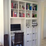 Wall system idea with white bookshelves and media desk a darker coated wooden chair with white cushion