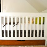 White BAby Crib With Storage Place Below And Fur Rug