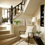White Color Of Room Entrance Near Stairs With White Chair And Standing Lamp