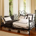 White bedding for wrought iron daybed brown bedcover with white polka dots pattern some decorative pillows in white dominant color three white rattan  boxes as additional storage