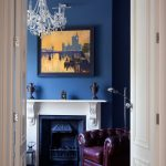 White fireplace mantel with standard height a beautiful painting with black frame as wall art navy blue wall paint a crystal pendant chandelier a dark brown leather corner chair with a metal floor lamp