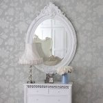 White framed antique mirror white storage system with classic white table lamp a blue vase with white flowers