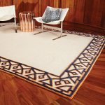 White global view rug with multiple patterns and colors in each edge of rug white chairs with a decorative pillow gold tone color round side table