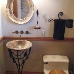 Wonderful vessel sink with black stained metal holder a round mirror with beautiful frame a toilet