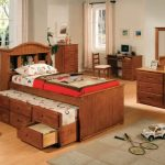Wood trundle with pull out bed frame and storage idea wood  bedroom vanity with wood framed mirror wood workstation and wood chair with white cushion a bedside table with drawers