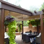 Wooden Patio Cover Design Decor With Hanging Plants And Grey Table Chair Set