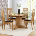 Wooden round table with four wooden chairs with black leather cushion for modern dining room