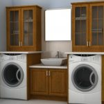 Wooden under cabinet with white vessel plus faucet on its top two upper cabinets with trimmed glass door  a frameless mirror two washer machines