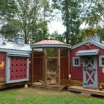 a-fancy-chicken-coop-with-mansion-design-with-red-and-white-color-combined-with-plants-on-the-left-right-side