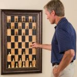 A Man Plays An Unusual Brown Wooden Straight Up Wall Mounted And Framed Chess Set With Black And Beige Chessboard Hang On The Wall