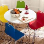 a round white table with stainless steel legs and colourful chairs for children