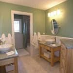 Adorable And Traditional Bathroom Idea With Natural Wooden Vanity And Dresser And Oval Wall Mirror And White Beadboard And Wall Lamp