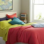 adorable coral color beddin sheet idea with blue pillows and orange and greena nd purple combination with large glass window