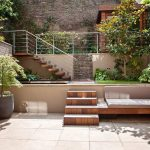 adorable lower courtyard idea with stairs and wire railing and plants and brick wall and concrete patio with woodne banquette and gray bolster