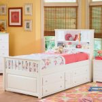 Adorable Pop Up Trundle Bed Frame Idea With Pink Floral Bedding Sheet And Storage Headboard And White End Table And Brown Drape And White Dresser And Colorful Rug