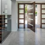 adorable sliding imga front door design with stone wall accent and frosted glass accent and wooden stairs and concrete flooring