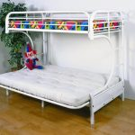 adorable white matress and colorful bedding in white frame of convertible bunk bed design on wooden floor with potted plant