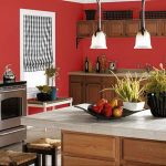 Amazing Red Color Kitchen Paint Idea With Wooden Cabinetry And Small Island And Wooden Stools And White Pendants And Potted Plants