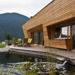 architectural contemporary wooden house design with open concept with concrete patio and pond and mountain view