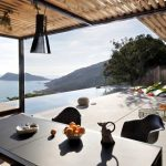 beach villa design with outdoor living space and canopy and seating bar with wooden table and mountain view