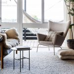 beige-ch445-wing-chair-by-hans-wegner-on-the-carpet-on-the-wooden-floor-with-cushions-and-book-on-the-small-table-also-beige-curtain-near-plants-on-pots-and-glass-windows-and-door
