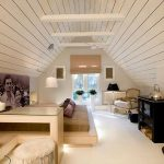 best loft bedroom idea with white wooden ceiling and beige beding with glass window and black storage with corner sofa