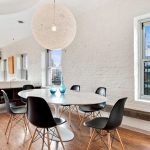 black-eames-molded-plastic-chairs-with-white-tulip-table-under-a-string-pendant-light-and-near-glass-windows-also-brown-wooden-floor