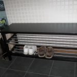 black wooden shoes and boot storage idea with stainless steel accent and black tile flooring and small tile wall