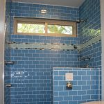 blue colored subway tile installed in modern and simple bathroom ideas with wall shower and glass ventilation