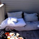 Casual Modern Balcony Idea With Vinyl Siding And Wooden Floor And Fence And Soft Floor Pillow And Black Coffee Table